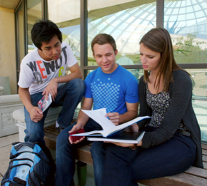 Photo: 3 students reading in front of library