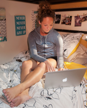 Photo: Girl studying with laptop and sign on wall says