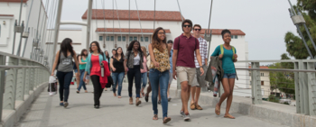 Photo: group of  students walk across SDSU bridge