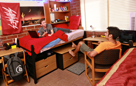 Photo: Two male students in residence hall room, one on bed