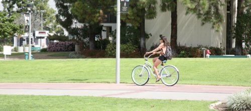 Photo: girl on campus riding bicycle