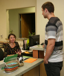 Photo: student and staff at front desk, SDSU Well-being & Health Promotions department