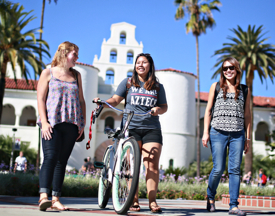 Photo: 3 SDSU women walking, one with a bike, in front of Hepner Hall