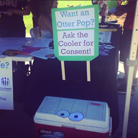 Photo: Health Promotion booth on campus offering free Otter Pps with sign: Want an Otter Pop? Ask the Cooler for Consent!