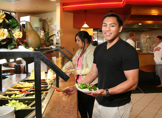 student serving themselves at the salad bar