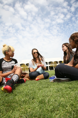 Photo: Group of women sitting on grass on campus