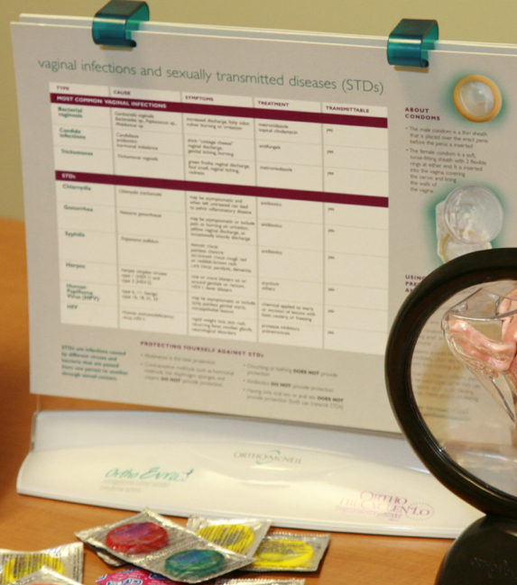 Photo: Sexual health presentation items including STD chart and condom packages