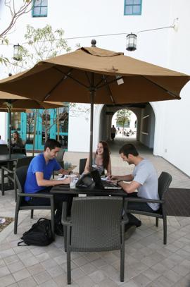 Photo: Students at table under umbrella