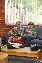 Photo: Guy and girl reading in residence hall