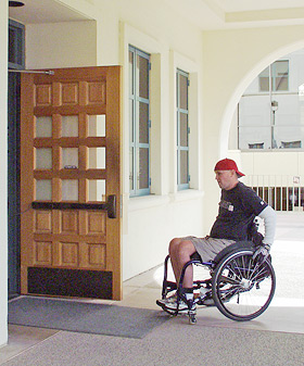 person in a wheelchair entering an office