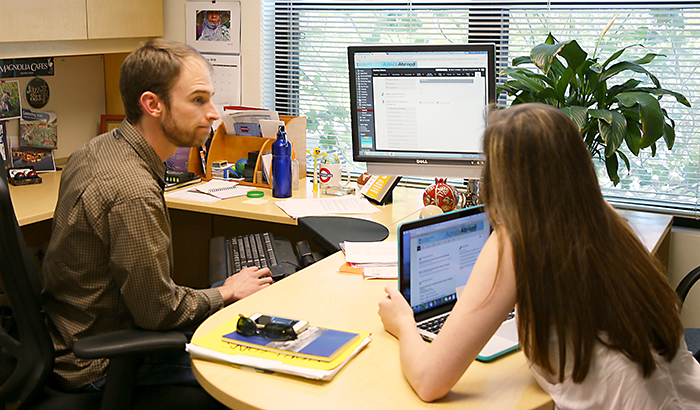 image of advisor at desk with student looking at study abroad online