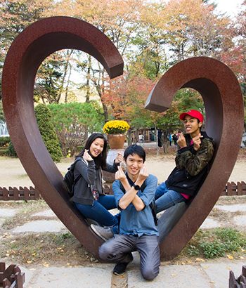 study abroad student blogger sitting in heart shaped sculpture.