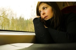 Photo: Female student aboard train looking unhappy and gazing out window