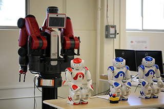 Photo of three little robots and a large red robot