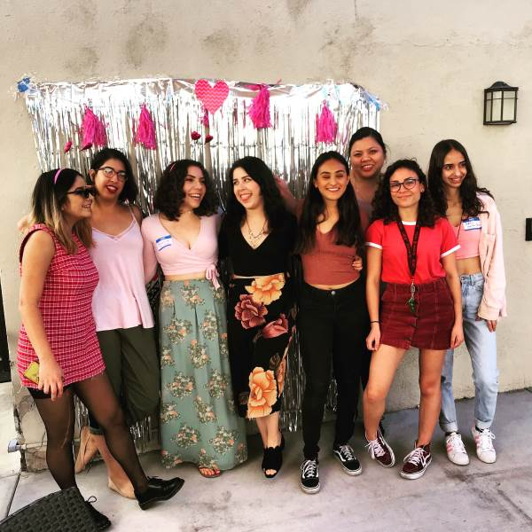 photo of group of girls standing in front of wall with streamers and hearts