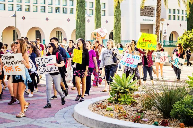 photo: students protesting on campus w/ Stop the Silence posters